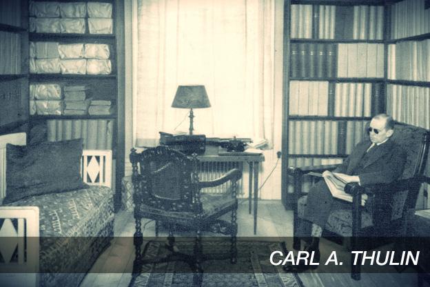 Bild av Carl A. Thulin. Sitter i stol och läser bredvid ett skrivbord omgiven av bokhyllor.